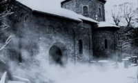 An isolated, medieval prison in a snowy setting
