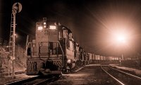 Rain in a small town at night, with a train passing through
